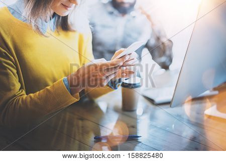 Young team of coworkers working together in modern coworking space.Woman sending message with smartphone. Man work on desktop computer.Horizontal, flare effect. Blurred background