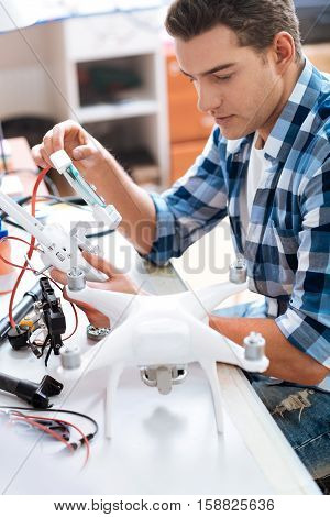 Be attentive. Concentrated young delighted man using remote controller and discovering drone landing gears while working with whole mechanism.