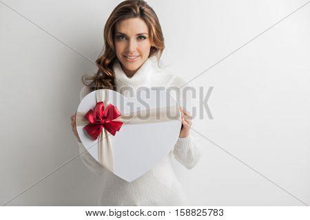 Beautiful woman holding heart shaped gift box