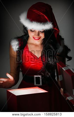 Woman in santa claus costume opening magic christmas gift