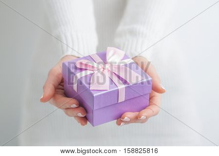 Woman holding small purple gift box in hands