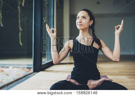 View of gorgeous young woman practicing yoga indoor. Beautiful girl practice ardha matsyendrasana in class.Calmness and relax, female happiness concept.Horizontal, blurred background