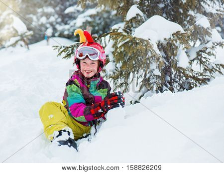 Happy kid with helmet on sitting and playing with snow