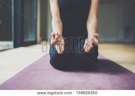 Closeup view of gorgeous young woman practicing yoga indoor. Beautiful girl practice ardha matsyendrasana in class.Calmness and relax, female happiness concept.Horizontal, blurred background