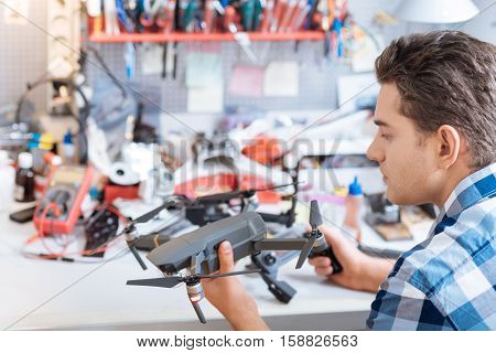 In usage. Young handsome smart man holding drone propeller and remore controller while testing the mechanism and sitting in a workroom.