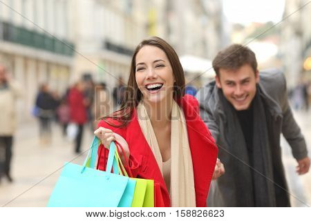 Front view of a casual couple of shoppers running in the street towards camera holding colorful shopping bags