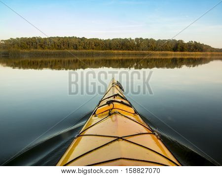 Point of view shot from inside kayak on glassy water