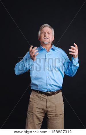 Feel this atmosphere. Grey-haired man enjoying the moment with closed eyes holding both hands in air while standing against black background