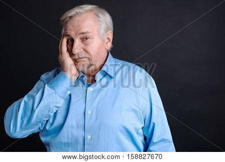 Feel depressed. Upset mature bearded man touching his face looking at camera wearing smart blue shirt, isolated on black background
