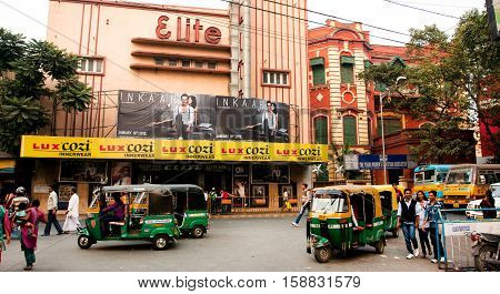 KOLKATA, INDIA - JAN 20, 2013: Auto rickshaw taxis and pedestrians move past the old cinema theater on January 20, 2013. Indian three-wheelers have the design of the Piaggio Ape C from 1948