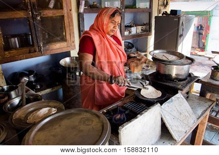 CHITRAKUT, INDIA - DEC 28, 2013: Senior indian lady in sari dress cooking national bread in small street cafe on December 28, 2012. Population of Chitrakoot is 22294. By the legend Lord Rama lived here