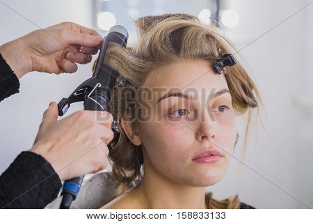 Professional hairdresser, stylist making curls in white make up room. Beauty and haircare concept