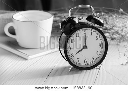 Black and white image of a clock on a wooden table,Clock displays the time eight o'clock,Clock on a wooden table with natural light