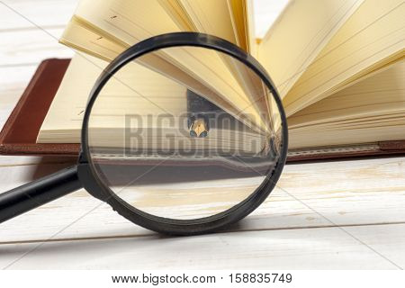 open book pen and magnifying glass. Back to school copy space. Education background.
