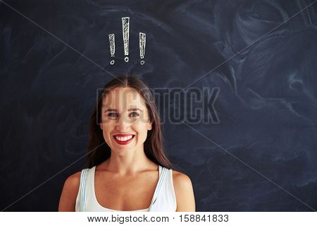 Pretty young woman is standing against blackboard with chalk exclamation marks drawn on it