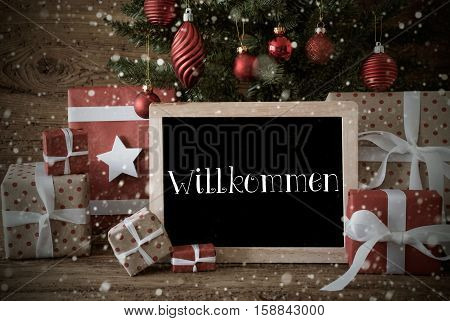 Nostalgic Christmas Card For Seasons Greetings. Christmas Tree With Balls And Snowflakes. Gifts In The Front Of Wooden Background. Chalkboard With German Text Willkommen Means Welcome