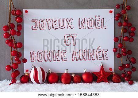 Label With French Text Joyeux Noel Et Bonne Annee Means Merry Christmas And Happy New Year. Red Christmas Decoration Like Balls On Snow. Urban And Modern Cement Wall As Background