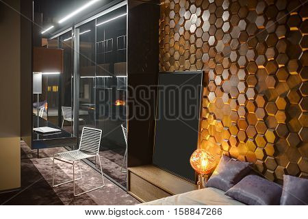 Modern bedroom with a carpet on the floor and a wooden wall textured with hexagons. There is a specular wardrobe, a white chair, wooden lockers and shelves, a bed with pillows, glowing lamps.