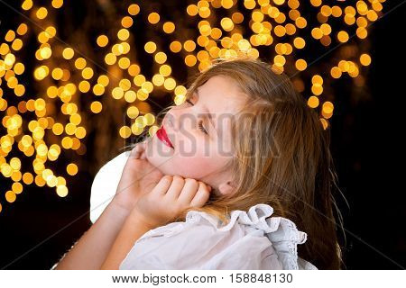 A blissful young girl with blond hair sits in front of a starry Christmas light background with her chin in her hands and head tilted back. She has closed eyes and a closed mouth smile.