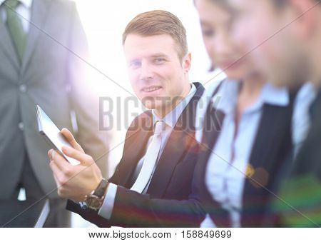 businessman posing in the meeting room while colleagues are working behind