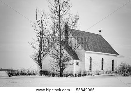 horizontal black and white image of an old rustic white wooden church sitting on a blanket of snow in the winter time.
