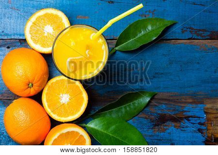 Fresh orange juice, fresh fruits orange with leaves on wooden blue background. top view, copy space