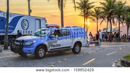 26 November 2016. Police car with policeman sitting in it on the background of a beautiful sunset with the orange sun, green palms and a big truck in Ipanema beach, Rio de Janeiro, Brazil