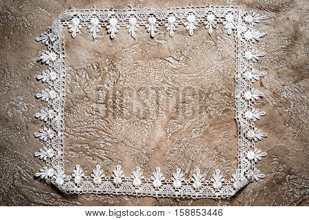 Frame Made Of White Lace Carelessly Stacked On A Neutral Beige Grunge Concrete Background