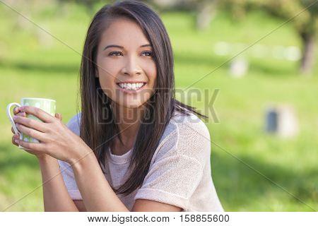 Beautiful happy Asian Eurasian young woman or girl outside drinking mug of tea or coffee