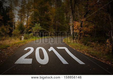 Happy New Year 2017 against country road along trees in the lush forest