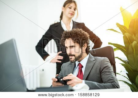 Businessman playing a pc game at work