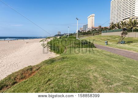 Quiet early morning grass verge and empty beach against commercial and residential buildings and blue sky on beach front in Amanzimtoti in Durban South Africa