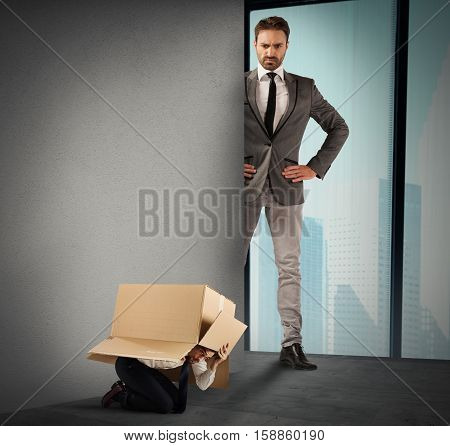Employed afraid hides in a box from his big boss