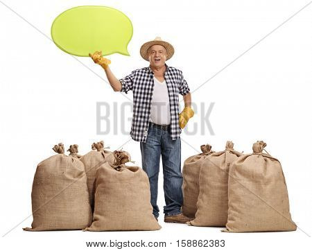 Full length portrait of a mature farmer standing between burlap sacks and holding a speech bubble isolated on white background