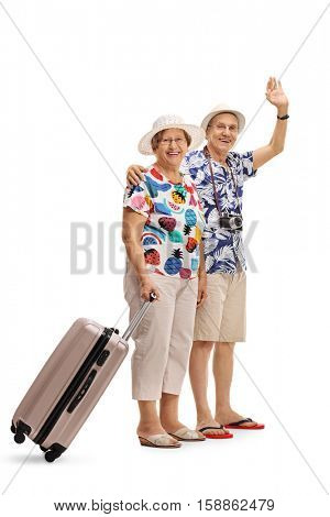Full length portrait of a mature female tourist with a suitcase and a mature male tourist waving isolated on white background