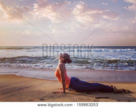 Vintage retro effect hipster style image of Yoga outdoors on beach - woman practices Ashtanga Vinyasa yoga Surya Namaskar Sun Salutation asana Urdhva Mukha Svanasana - upward facing dog pose on sunset