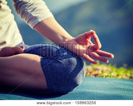 Close up of woman in Padmasana yoga lotus pose with chin mudra outdoors with copyspace. Vintage retro effect filtered hipster style image.