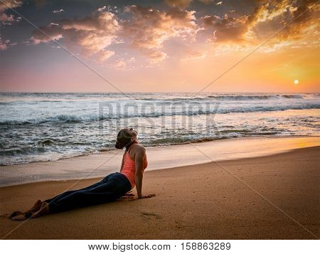 Vintage retro effect hipster style image of Yoga outdoors - woman doing Ashtanga Vinyasa yoga Surya Namaskar Sun Salutation asana Urdhva Mukha Svanasana upward facing dog pose on sunset on beach