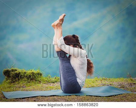 Yoga - sporty fit woman practices Ashtanga Vinyasa yoga asana Urdhva mukha paschimottanasana - upward facing intense west stretch oudoors. Vintage retro effect filtered hipster style image.