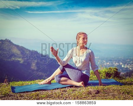 Yoga exercise outdoors -  woman doing Ardha matsyendrasanaasana asana - half spinal twist pose mountains in Himalayas in India in the morning. Vintage retro effect filtered hipster style image.