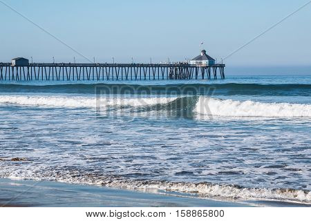 Imperial Beach, California fishing pier with beach and waves in foreground.