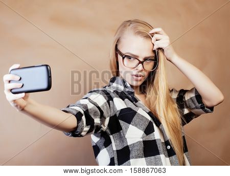 young pretty blond hipster girl making selfie on warm brown background, lifestyle people concept close up