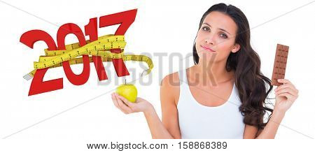 Pretty brunette deciding between apple and chocolate against digitally generated image of 3D new year with tape measure