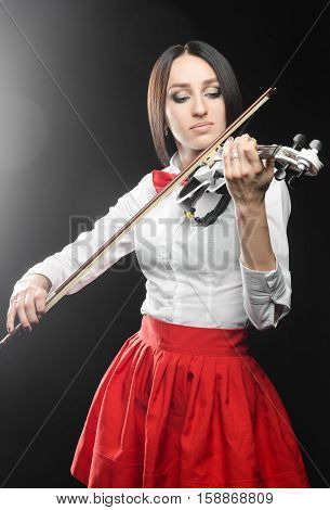 Beautiful woman playing the violin on a black background closing her eyes