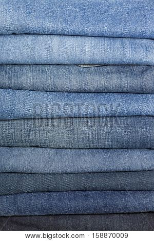 Stack Of Jeans Folded On White Background - Various shades of color.