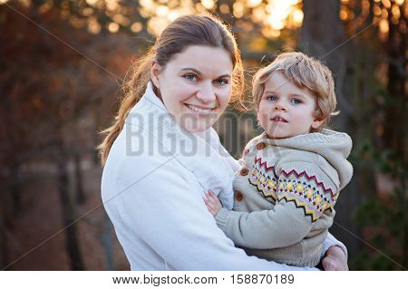 Mother and little son in spring park or forest, outdoors. Hugging and having fun together. Happy toddler boy and young mum, kid and woman playing. Woman and son in love.