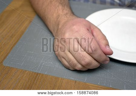 Male hand laid next to the empty plate on a table closeup concept shot