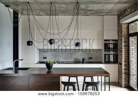 Kitchen in a loft style with concrete and brick walls. There is a kitchen island with a sink, plant and black chairs, light lockers with built-in oven and fridge, dark tabletop with stove and teapot.