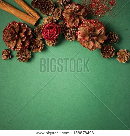 Top view of the frame of pinecone and cinnamon on the green paper background