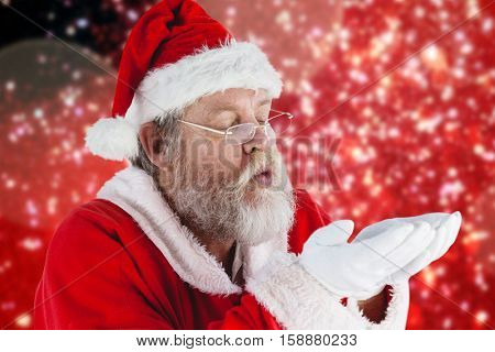 Santa Claus in eyeglasses blowing invisible snow against white snow and stars on red